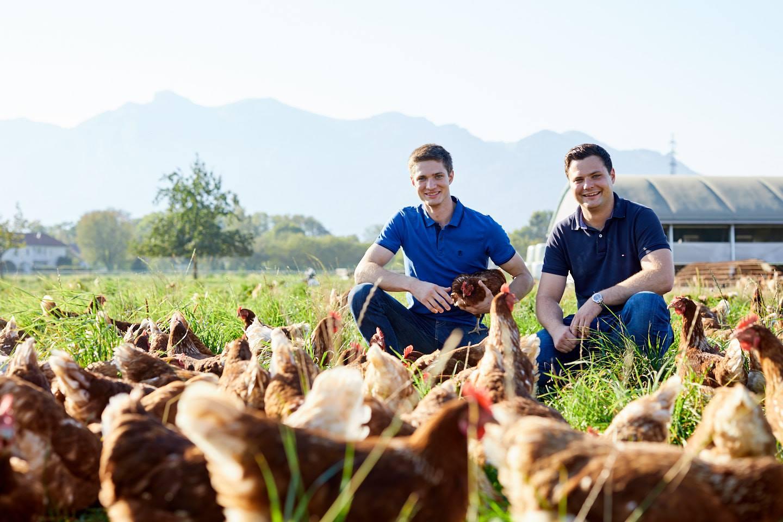 Johannes Und Mathias Allgäuer Sitzen Auf Einer Wiese Umringt Von Hühnern