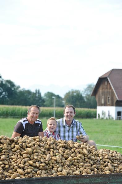 Familie Ludescher Sitzt Auf Einem Anhänger, Welcher Mit Kartoffeln Gefüllt Ist, Dabei Lächeln Sie In Die Kamera