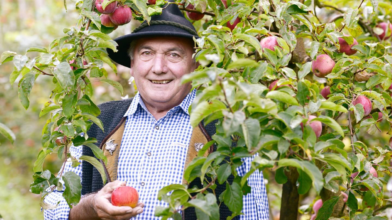 Toni Schiefer Schaut Lächelnd In Die Kamera, Einen Ländle Apfel In Der Hand Haltend Und Unter Einem Seiner Apfelbäume Stehend