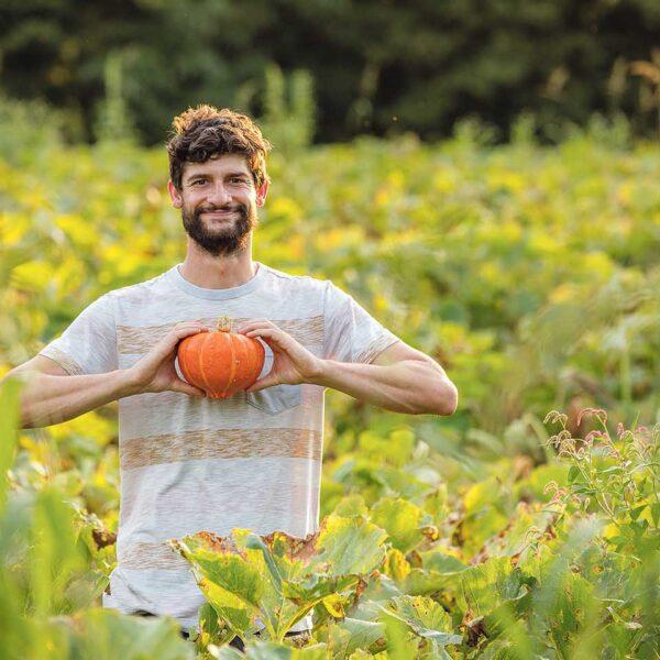 Johannes Hämmerle mit einem Kürbis auf seinem Feld